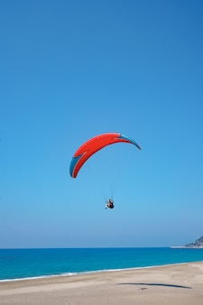 Paraglider tandem flying over the sea shore with blue water and sky on horison. view of paraglider and blue lagoon in turkey.
