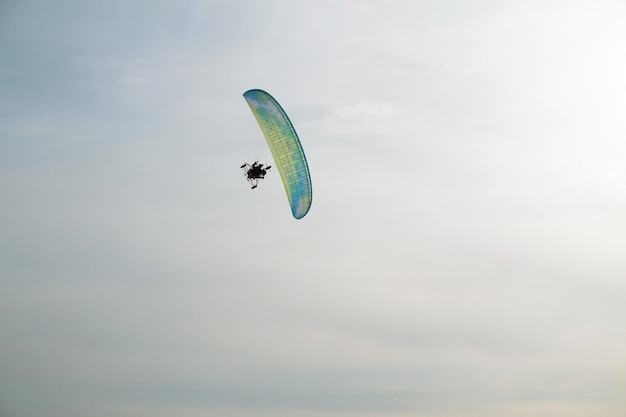 Paraglider with motor flies over the sea, which is covered with ice and snow