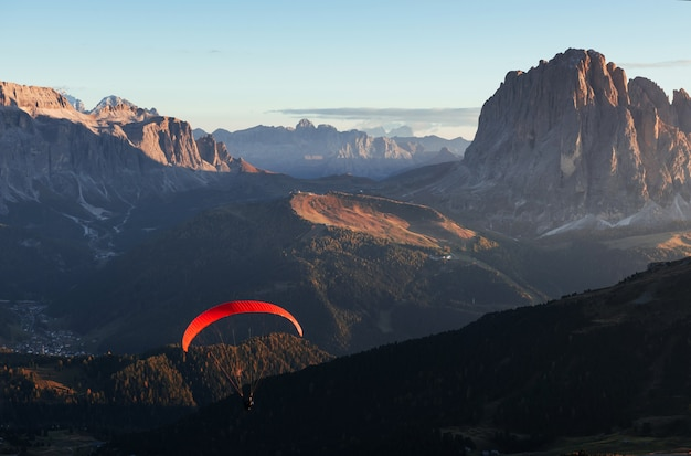 Paraglider with red parachute flies over the mountains filled with trees in the sunlight.
