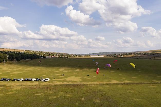 Силуэт параплана пролетел над красивым зеленым пейзажем под голубым небом с облаками.