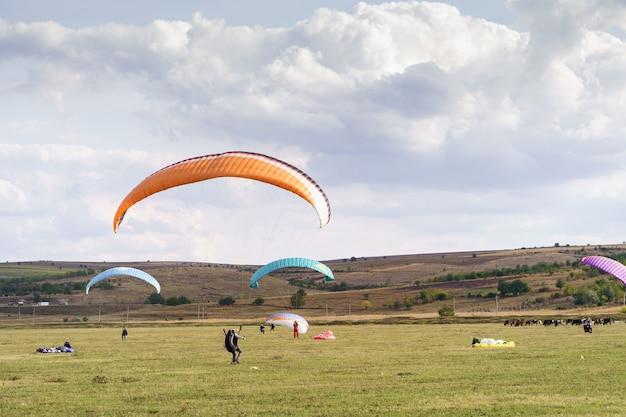 구름과 푸른 하늘 아래 아름 다운 녹색 풍경을 비행하는 패러 글라이더 실루엣.