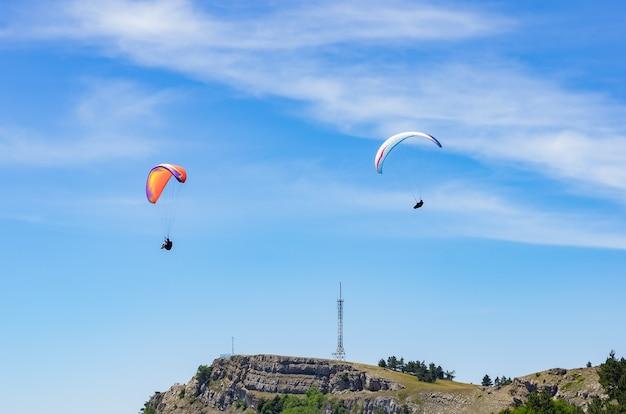 산 정상 위로 날아오르는 패러글라이더