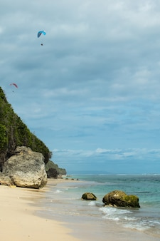 Paragliders take off from a green mountain against the background of a sea beach and a blue sky with clouds