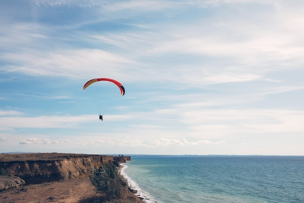 Paragliders tandem in blue sky over the sea shore