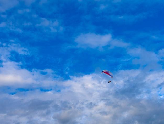 青い空のエンジンを搭載したパラグライダー