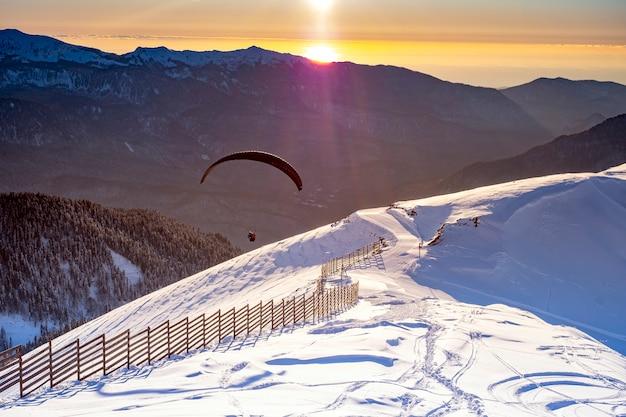 山の冬の夕暮れ時のパラグライダー