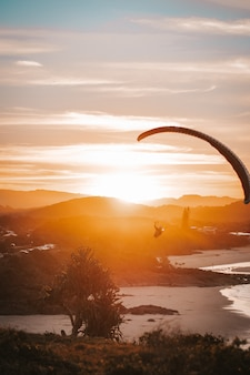 Paragliding on the beach with sunset