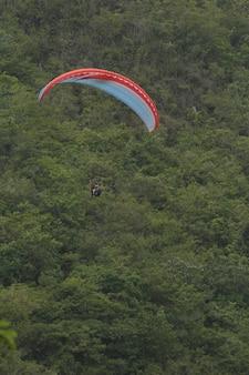 木の包帯で山の上を飛んでいるパラグライダー