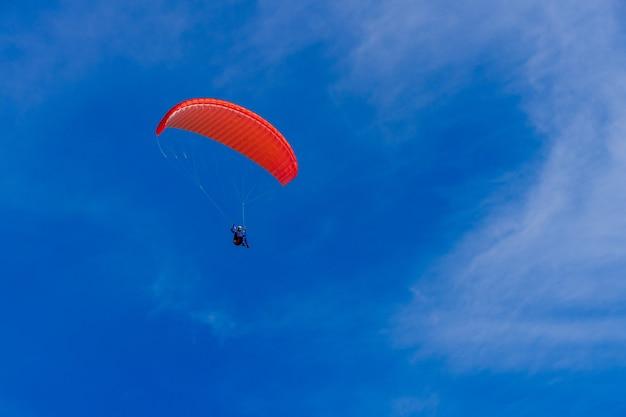 Полеты на параплане в голубом небе. парашют с парапланом летит. экстремальные виды спорта, концепция свободы