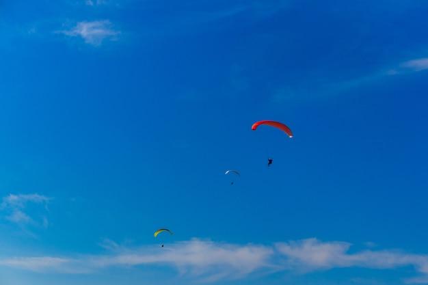 푸른 하늘에서 패러글라이딩. 패러글라이더가 달린 낙하산이 날고 있습니다. 익스트림 스포츠, 자유 개념
