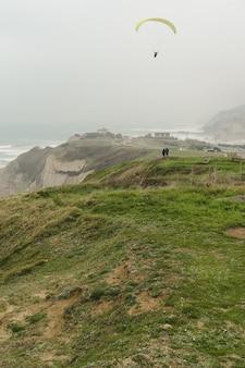 Полет на параплане над зелеными скалами в пасмурный день