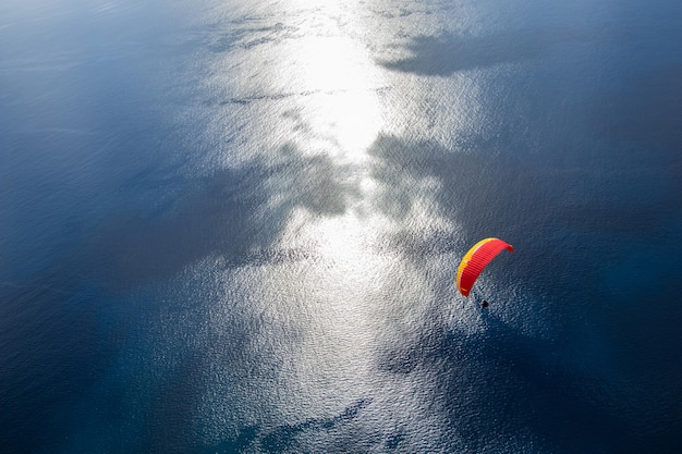 Paragliding in the sky. flying over the atlantic ocean with blue water in bright sunny day. aerial view of paraglider on madeira island, portugal. extreme sport.