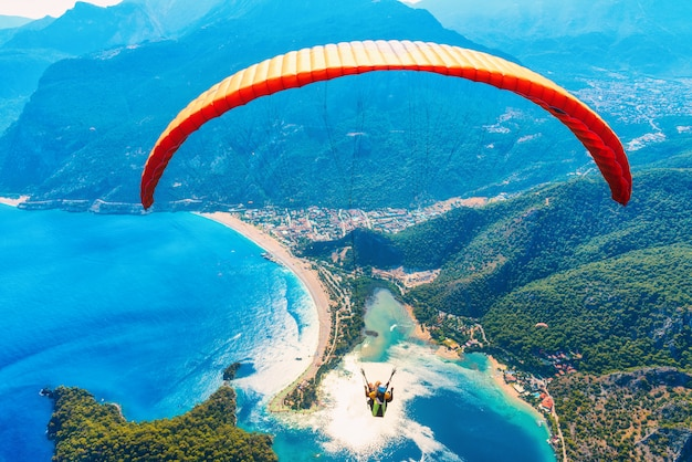 Paragliding in the sky. paraglider tandem flying over the sea with blue water and mountains in bright sunny day.