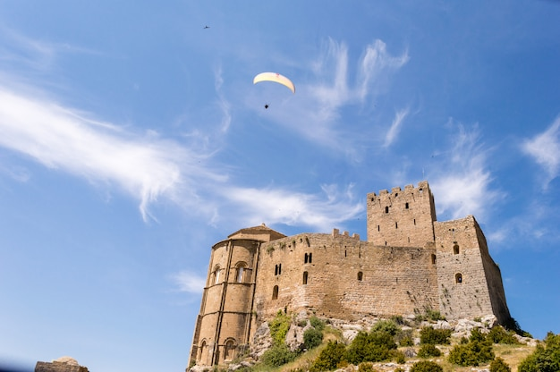Paragliding in the sky. paragliders flying over the medieval castle of loarre, huesca, spain