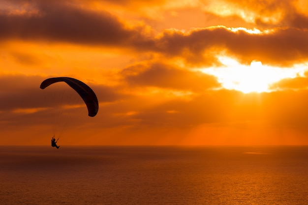 Paragliding at sunset with amazing cloudy sky and sun shining through clouds