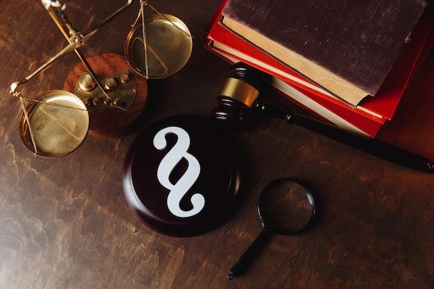 Символ абзаца и судья молоток с весами и книгами.