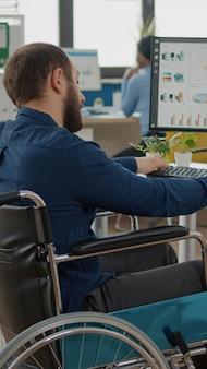 Парализованный менеджер, работающий в офисе запуска бизнеса, сидя в инвалидной коляске