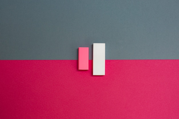 Parallel erasers on pink and gray background