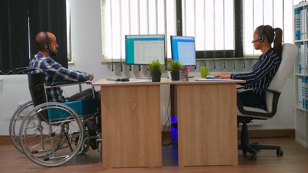 휠체어를 탄 마비된 사업가가 헤드셋을 사용하여 텔레마케팅을 하고 고객 지원을 제공합니다. 현대 기술을 사용하여 금융 회사 건물에서 일하는 고정 장애인 프리랜서