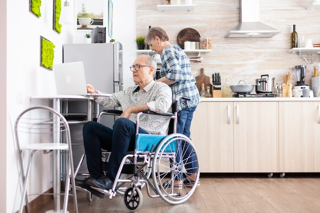 Paralysed elderly man in wheelchair typing on laptop working from home at computer in kitchen while wife is cooking breakfast. handicapped businessman, entrepreneur paralysis for elderly retired male