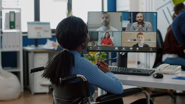 車椅子に固定されて座っている麻痺した障害者の黒人労働者が、営業所の遠隔地の同僚とオンラインで話し合っているビデオ会議を行っている