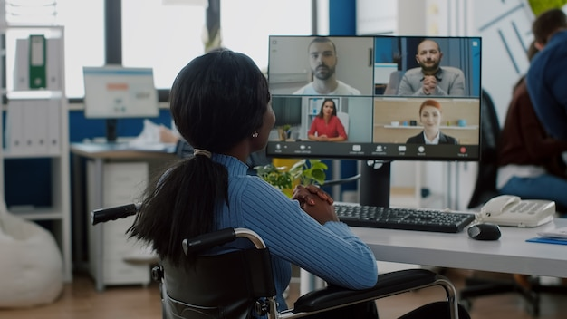 Paralysed handicapped black worker sitting immobilized in wheelchair having videomeeting discussing online with remotely colleagues in business office