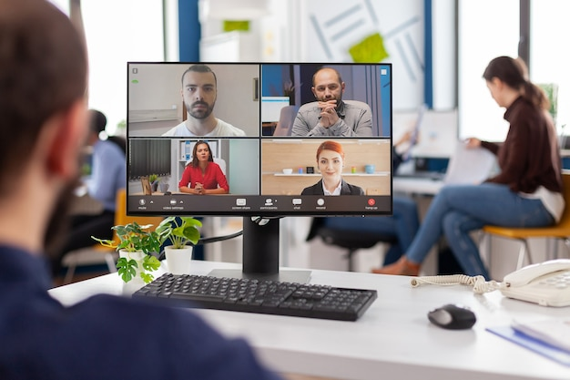 Paralysed handicapped businessman sitting immobilized in wheelchair having videomeeting discussing online with remotely colleagues in business office. invalid employee working in financial company.