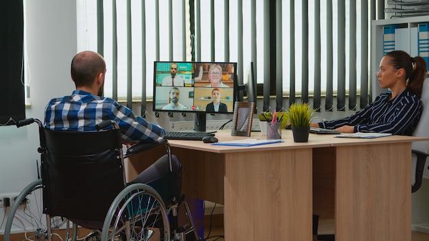비즈니스 사무실에서 동료들과 온라인으로 토론하는 화상 회의를 하는 휠체어를 탄 마비되고 움직이지 않는 프리랜서. 현대 기술을 사용하여 금융 회사에서 일하는 장애인 사업가.
