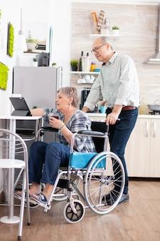 タブレットコンピューターで働いている車椅子の麻痺した先輩妻は、台所に座っている彼女のプロジェクトを夫に示しています。現代の通信オンラインインターネットを使用して障害のある高齢者高齢者w 無料写真