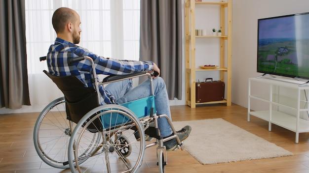 テレビを見ている車椅子の麻痺し、落ち込んでいる若い男。