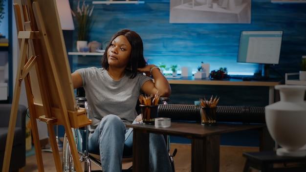 キャンバスに描く車椅子に座っている麻痺した黒人アーティスト