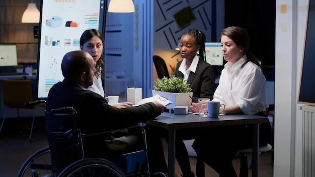 夜遅くに営業所の会議室で働いている間、車椅子で麻痺したビジネスマンは無視されます。会社の戦略のアイデアをブレインストーミングする多様な多民族のビジネスマン