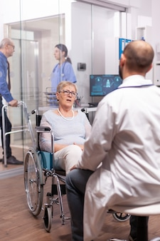 Paralyzed discussing with geriatrician sitting in wheelchair in the course of examination