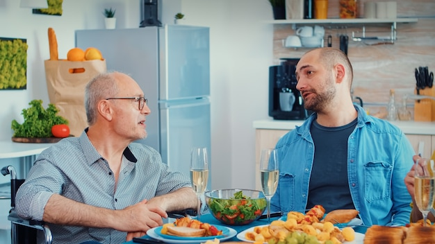 Paralyzed father talking with his son sitting in wheelchair during the family dinner. happy couples smiling and eating during a gourmet meal, enjoying time sitting around the table in the kitchen