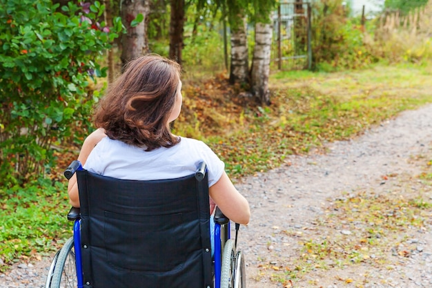 Paralyzed girl in invalid chair for disabled people outdoor in nature