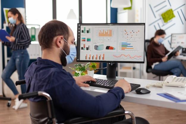 スタートアップ企業のオフィスで働くコンピューターでのcovid19タイピングマーケティング戦略に対する保護フェイスマスクを備えた麻痺した障害のあるビジネスマン。統計を分析する無効なマネージャー
