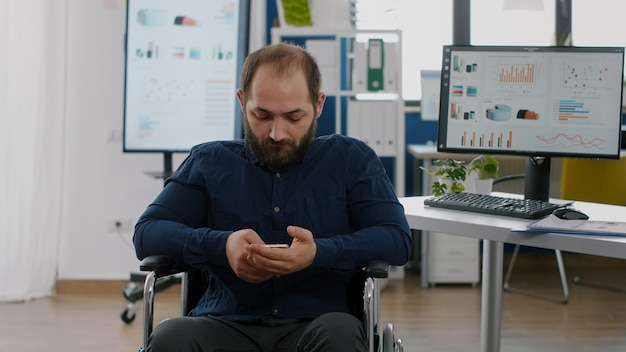 Paralyzed immobilized disabled entrepreneur holding smartphone texting, browsing during work time sitting in wheelchair taking break