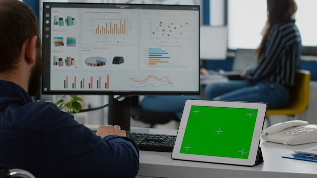 금융 통계를 분석하는 휠체어에 앉아 마비 된 잘못된 장애인 사업가, 녹색 화면 크로마 키로 태블릿을보고 izolated 데스크탑 계획 사업 프로젝트를 모의