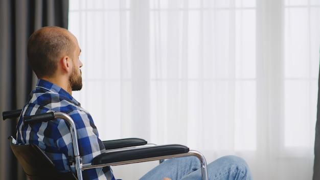 居間の車椅子に座っている麻痺した若い男。