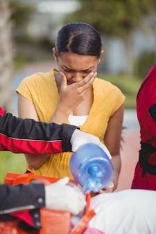 負傷した女の子に酸素を与える救急救命士
