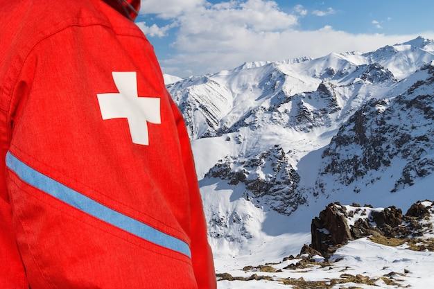 Фельдшер на склоне горы в красной одежде с белым крестом