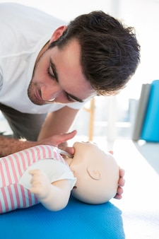 Paramedic practising resuscitation on dummy