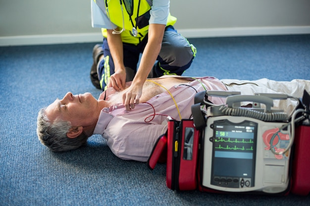 Paramedic using an external defibrillator on an unconscious patient
