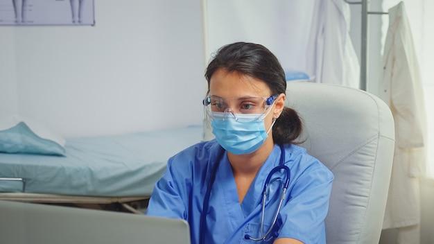 코로나바이러스 동안 노트북에 글을 쓰는 의사 사무실에 앉아 보호 마스크를 쓴 구급대원. 병원 캐비닛에서 의료 서비스 상담 치료를 제공하는 의학 전문의