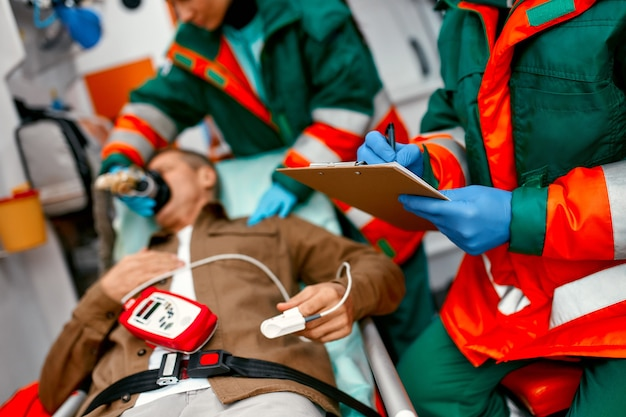 A paramedic woman in uniform puts on a ventilator with oxygen to help a senior patient lying with a pulse oximeter on a gurney in a modern ambulance. a male paramedic looks at a patient's chart.