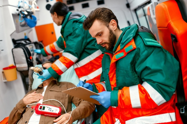 A paramedic woman in uniform puts on a ventilator with oxygen to help senior patient lying with a pulse oximeter on a gurney in modern ambulance. the male paramedic takes notes on the patient's card.