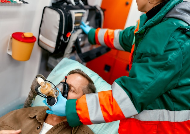 A paramedic woman in uniform puts on a ventilator with oxygen to help a senior patient lying with a pulse oximeter on a gurney in a modern ambulance.
