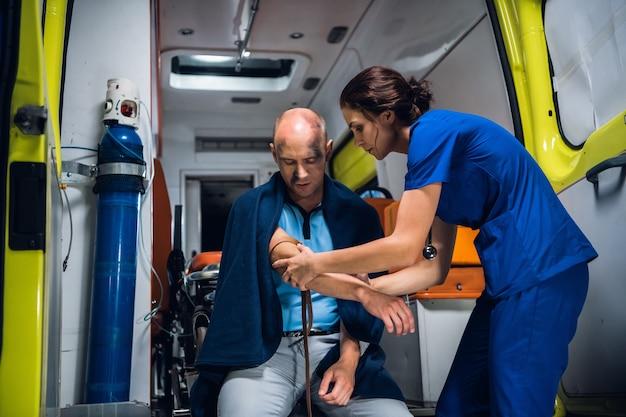 救急隊員は、救急車で負傷した男性の手に止血帯を巻き付けます。