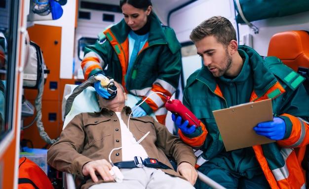 Парамедики работают с пожилым пациентом, когда он лежит на носилках в машине скорой помощи.