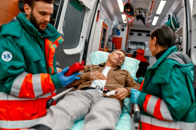 Paramedics check the level of oxygen in the blood and transport the elderly patient's gurney from the modern ambulance for further medical care at the clinic.